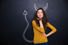 Cute woman with devils horns and tail drawn on blackboard Royalty Free Stock Images