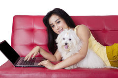 Cute woman and dog with laptop on sofa Stock Photo