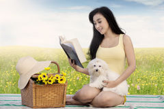 Cute woman and dog read book at field Stock Photos