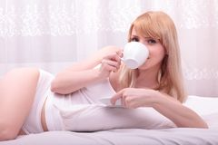 Cute woman drinking a coffee lying Royalty Free Stock Photography