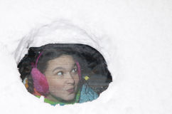 Cute woman driver surprised looking from behind a snowy car window Royalty Free Stock Photography