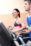 Cute woman with earphones exercising on treadmill Royalty Free Stock Photo