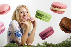 Cute woman eating macaroons. Big macaroons in background, photo manipulation Stock Photos