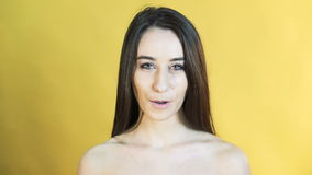 Cute woman with emotion of corageous on yellow background 4K stock video