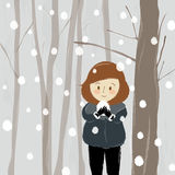 Cute woman enjoy snow fall with forest background. Stock Photography