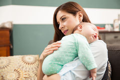 Cute woman enjoying motherhood. Portrait of a pretty Hispanic women holding her sleeping newborn baby and enjoying motherhood at home royalty free stock photos