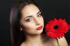 Cute woman Europeans, light make-up on her face in her hands and her hair pink gladiolus flowers. Female portrait. Woman with flow. Ers in her hair. Woman and Stock Photo