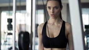Cute woman exercising in the gym. Attractive brunette with slender physique and cute face doing exercise on simulator. One person 20s 30s with sports clothing stock footage