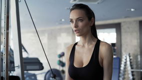 Cute woman exercising in the gym. Brunette with cute face working out exercise on simulator. One person 20s 30s with sports clothing train indoors interior stock video