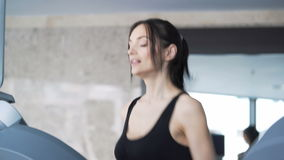 Cute woman exercising in the gym. Portrait of 20s with sports clothing train in gym indoors. Build beauty and vitality, endurance. slender brunette smile close stock footage