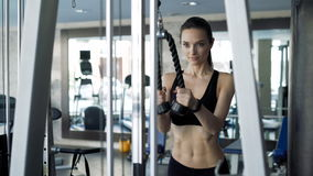 Cute woman exercising in the gym. Sexy attractive brunette with cute face working out exercise on simulator. One real 20s 30s with sports clothing train indoors stock footage