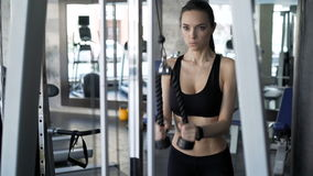 Cute woman exercising in the gym. Sexy attractive brunette with cute face working out exercise on simulator. 20s 30s with sports clothing train indoors interior stock video