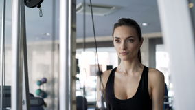 Cute woman exercising in the gym. Sexy brunette with slender physique and cute face doing exercise on simulator. One real human 20s 30s with sports clothing stock video footage