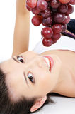 Cute woman face with red grapes Royalty Free Stock Images