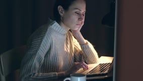 Cute woman falls asleep working at the laptop at night.