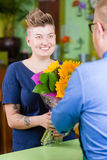 Cute Woman in Flower Shop Purchases Sunflowers Royalty Free Stock Photography
