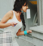 Cute woman gets cash from atm Stock Photos