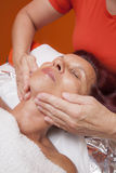 Cute woman gets professional facial massage, lymphatic drainage Stock Image