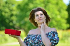 Cute woman with gift at summer park Stock Images