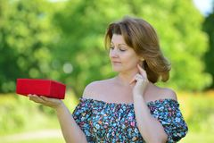 Cute woman with gift at summer park Stock Photo