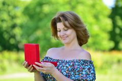Cute woman with gift at summer park Stock Image