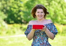 Cute woman with gift at summer park Stock Photos