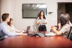 Cute woman giving a presentation. Pretty Hispanic brunette giving a presentation to her colleagues in a conference room Royalty Free Stock Photography