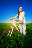 Cute woman in a green field on a bike Stock Images