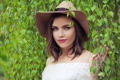 Cute woman in hat outdoors portrait. Pretty girl on green birch leaves background royalty free stock photos