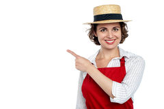 Cute woman in hat pointing sideways Royalty Free Stock Photography