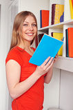 Woman holding book and looking at camera Stock Images