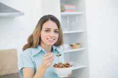 Cute woman holding a bowl with cereals while smiling at camera Stock Images
