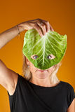 Cute woman holding a cabbage as a mask Royalty Free Stock Image