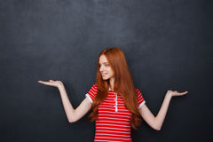 Cute woman holding copyspace on two palms over blackboard background Stock Photos