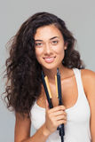 Cute woman holding hair straightener Stock Photos