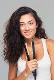 Cute woman holding hair straightener Stock Photos