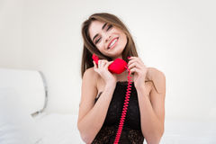 Cute woman holding red phone tube Royalty Free Stock Photography