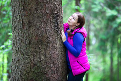 Cute woman hugging a big pine tree trunk Stock Images