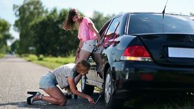 Cute woman jacking up her car to change flat tire stock video footage