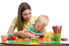 Cute woman and kid boy playing plasticine toys at home stock photos