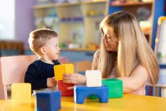 Cute woman and kid child playing educational toys at kindergarten or nursery room royalty free stock image