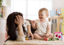 Cute woman and kid play together indoor Royalty Free Stock Photos