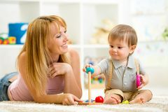 Cute woman and kid playing together indoor. Cute women and kid play together indoor Stock Photo