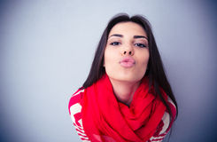 Cute woman kissing at camera over gray background Royalty Free Stock Photography