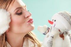 Cute woman kissing little snowman. Winter fashion. Stock Photography