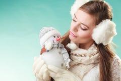 Cute woman kissing little snowman. Winter fashion. Stock Photos
