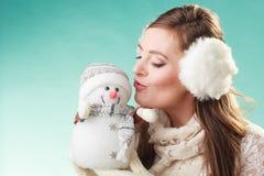 Cute woman kissing little snowman. Winter fashion. Stock Image