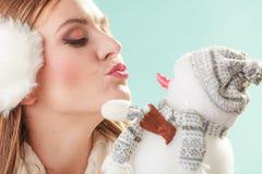 Cute woman kissing little snowman. Winter fashion. Royalty Free Stock Image