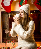 Cute woman in knitted sweater drinking hot tea next to fireplace Royalty Free Stock Image