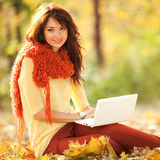 Cute woman with laptop in the autumn park Royalty Free Stock Photo